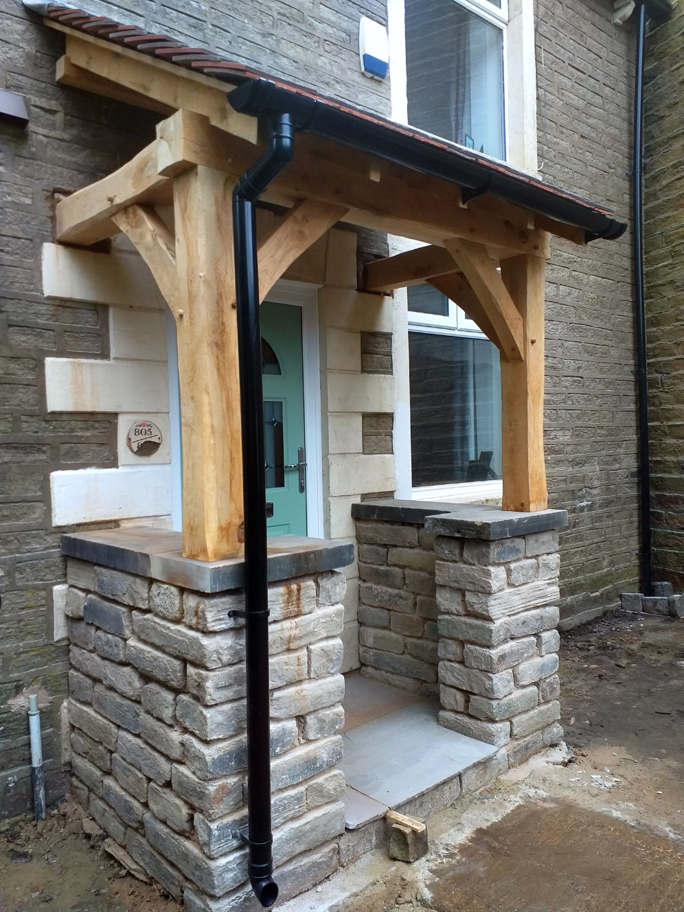 Side view, Porch with traditional Oak Frame, stone work, pitched roof complete with rain gutters